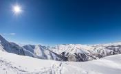 Sun star glowing over snowcapped mountain range, italian Alps