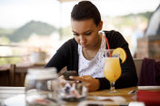 Young woman texting on the phone at a cafe
