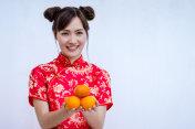 Asian woman with cheongsam holding orange. Chinese new year.