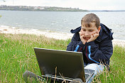 boy with notebook on river shore