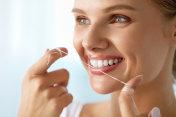 Teeth Care. Beautiful Smiling Woman Flossing Healthy White Teeth