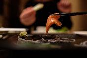 salmon sushi on chop stick
