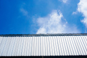 Wall and roof of Factory or warehouse building under blue sky with clouds