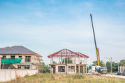 House building at construction site with crane truck