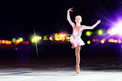 Young girl figure skating on ice with blurred lights in back