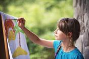 Little girl painting on easel in the garden