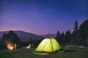 Illuminated  green  tent under stars at night  forest