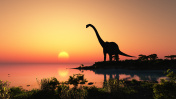 Silhouette of dinosaur at a lake at sunset