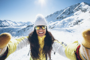 Smiling young woman having fun in the snow mountain