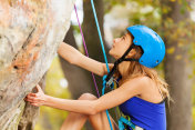 Young woman rock climbing to top of the mountain