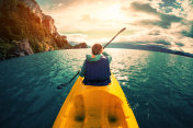 Woman paddles kayak in the lake with turquoise water