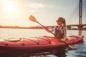 Woman kayaking on sunset