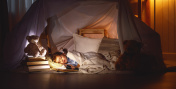 child girl sleeping in tent with  book and flashlight