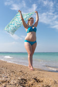 Overweight middle-aged woman with pareo walks along seashore