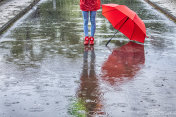 Low section of girl with umbrella