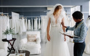 Dress designer fitting bridal gown to woman in boutique