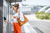 Woman buying a ticket or using ATM outdoors