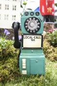 A green pay phone , little call box