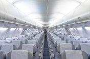 Commercial aircraft cabin with rows of seats down the aisle.