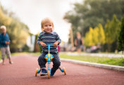 Cute little boy riding his tricycle in the park.