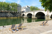 Deck chairs in the sun on the bank of the river Seine