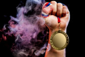 Man hand holding a gold medal