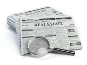 Real estate classifieds ads newspaper  and magnifying glass