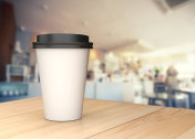 Coffee cup on the wood table with blurred background.