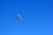 Soap bubble flying against the blue sky