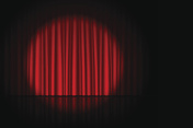 Stage with red curtain and spotlight on it
