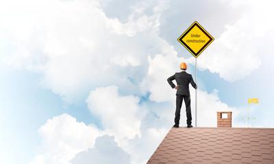 年轻工程师对砖屋顶持有安全标志指示在施工中的注意事项。混合媒体