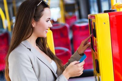 女人在公交车上使用售票机