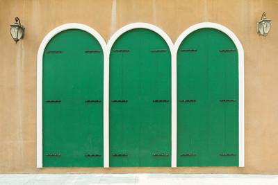 木墙和绘画与三个绿色门模式