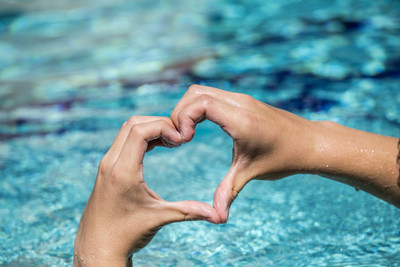 年轻人与心形状由手迹象的爱