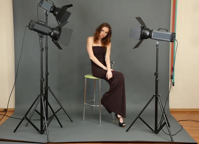 在摄影工作室拍摄设置射击之间休息的美丽专业女模特