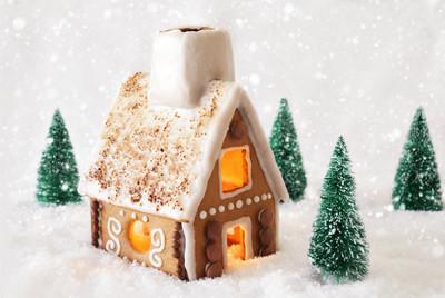 在雪雪花与白色背景上的姜饼屋