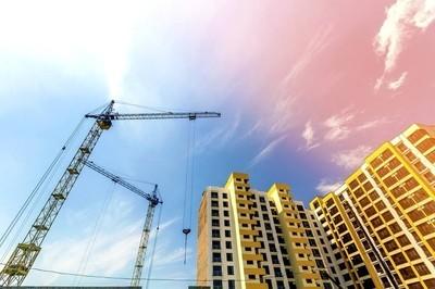 起重机和高层建筑在建设蓝天的映衬下