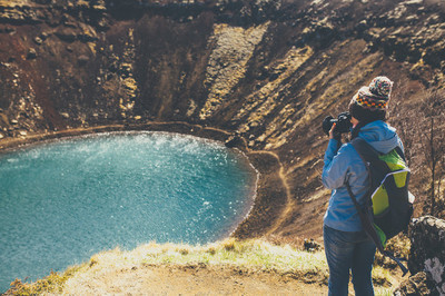 Back view of woman taking pictures in  crater