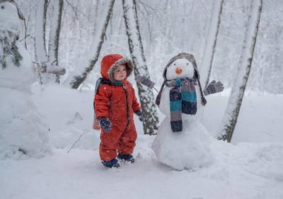 欧洲男孩和雪森林里的雪人