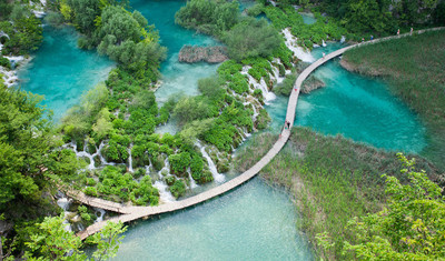 Top view of  Plitvice Lakes with waterfalls and wooden walkways with tourist