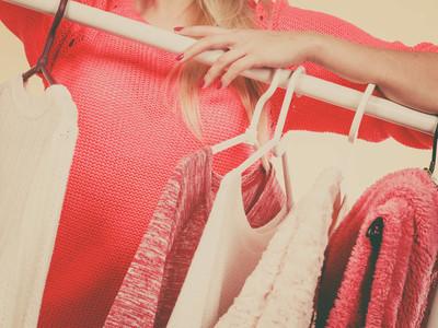 购物, 装备理念的概念。女手在服装店、衣柜或时尚精品馆内挑选衣架上的衣服