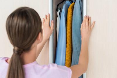 近距离拍摄的年轻女子打开橱柜与衣服在家里