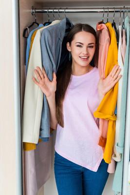 家中挂着衣服的微笑的年轻女子站在橱柜里
