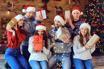 快乐的朋友与礼物在圣诞节微笑