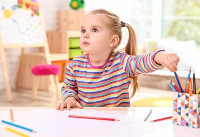 小可爱的女孩在桌子上画画