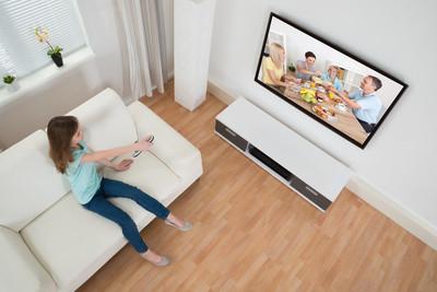女孩抱着遥控器在电视机前