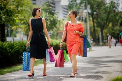 两个年轻时髦女装走在街上手中购买