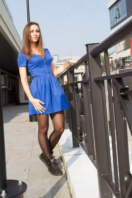 在办公大楼为背景的蓝色短裙的年轻姑娘