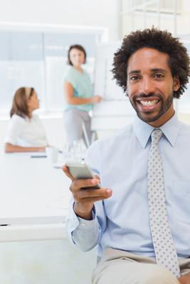 微笑的商人发短信与办公室的同事