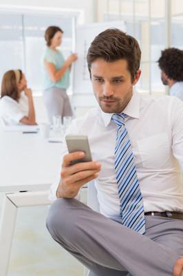 商人发短信与同事在会议上